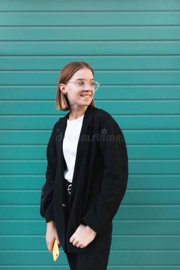 Porträt eines lächelnden Mädchens in einem stilvollen Kleid gegen einen Hintergrund einer Türkiswand glücklich stockbild