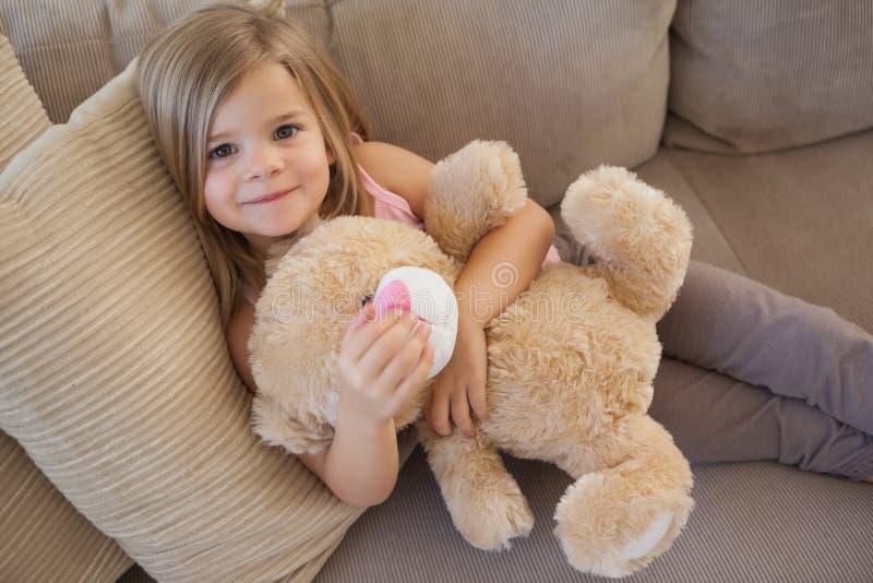 Porträt eines lächelnden Mädchens mit dem angefüllten Spielzeug, das auf Sofa sitzt lizenzfreie stockbilder