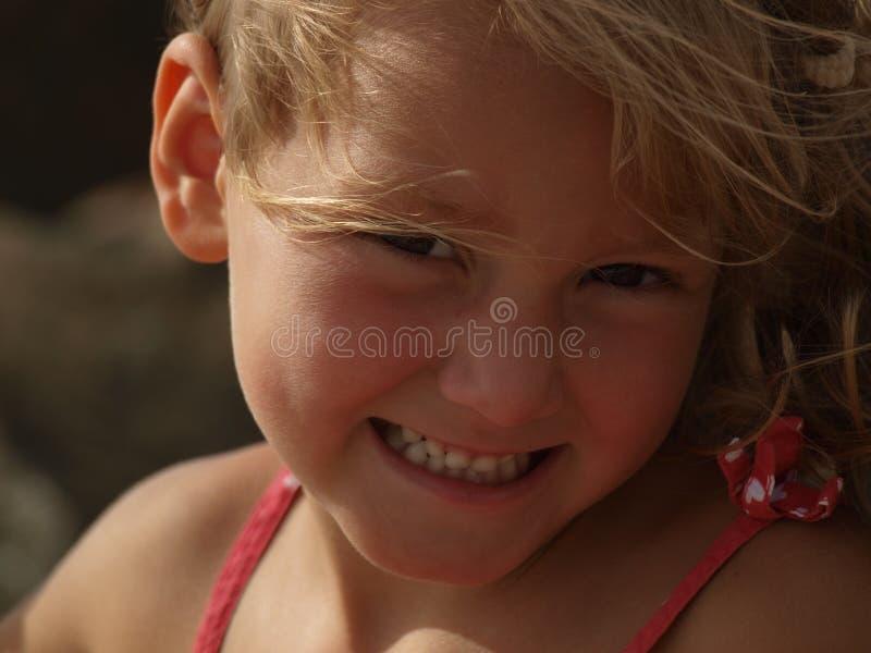 Porträt eines lächelnden Mädchens mit dem blonden Haar, das im Wind sich entwickelt stockfotografie