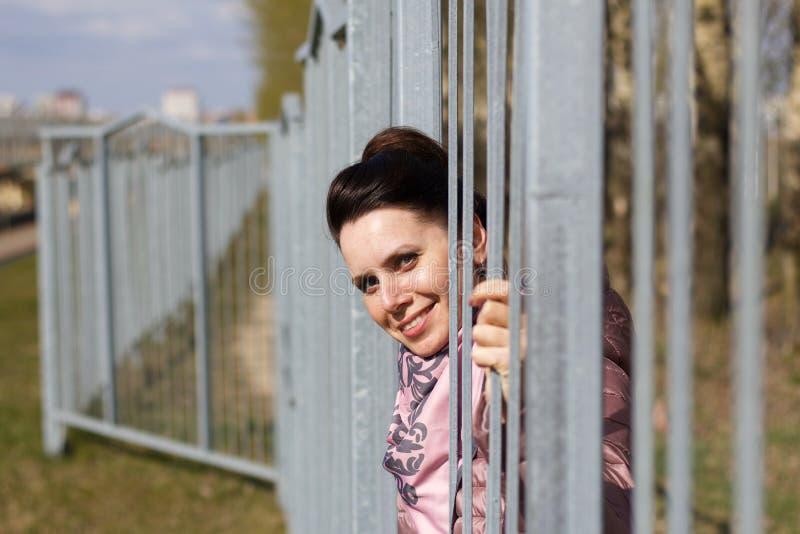 Porträt eines lächelnden Mädchens Sie schaut durch die Gitter eines Metallzaunes In einer Federjacke verkleidet, um den Nacken lizenzfreies stockbild