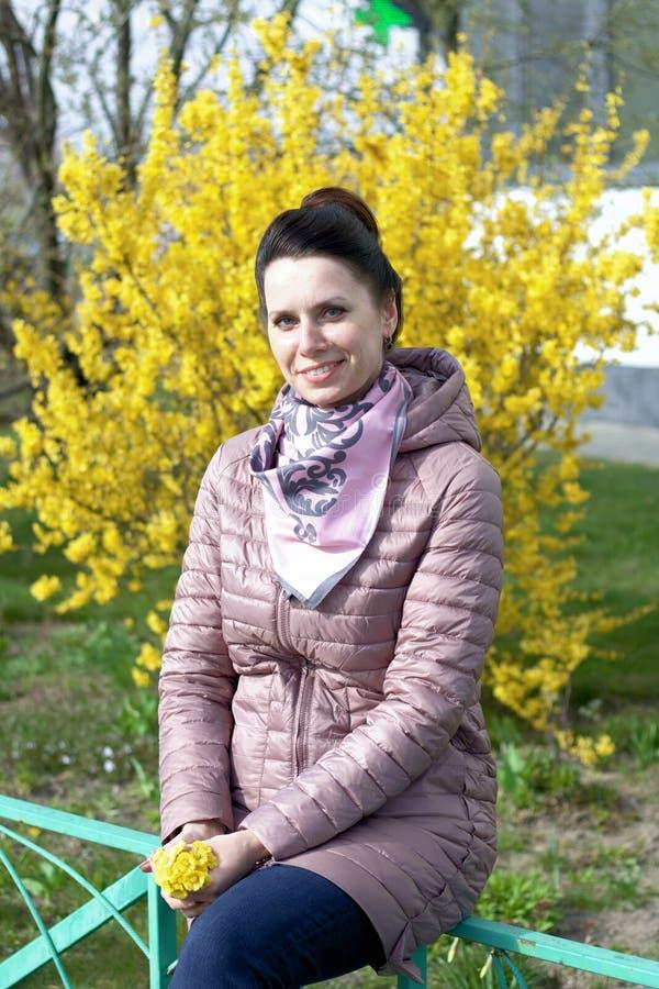 Porträt eines lächelnden Mädchens Vor dem Hintergrund eines mit gelben Blumen bepflanzten Buschs in den Händen eines Strauquets v stockbild