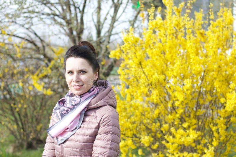 Porträt eines lächelnden Mädchens Vor dem Hintergrund eines mit gelben Blumen bepflanzten Buschs In einer Federjacke verkleidet,  stockfotografie