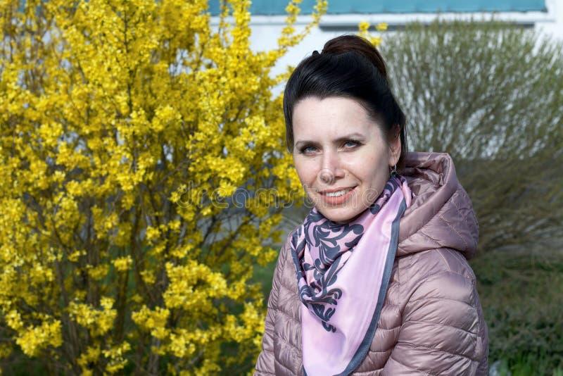 Porträt eines lächelnden Mädchens Vor dem Hintergrund eines mit gelben Blumen bepflanzten Buschs In einer Federjacke verkleidet,  lizenzfreies stockbild