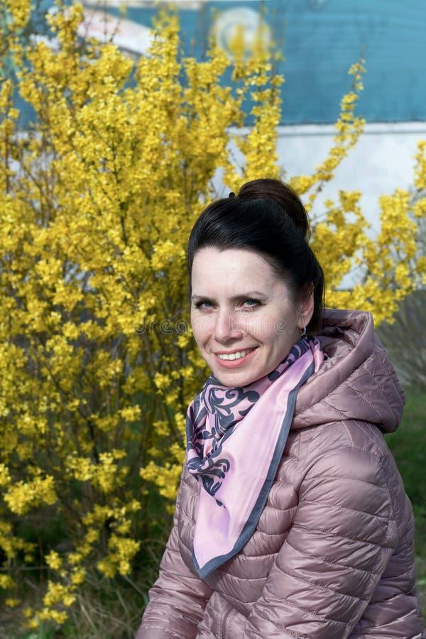 Porträt eines lächelnden Mädchens Vor dem Hintergrund eines mit gelben Blumen bepflanzten Buschs In einer Federjacke verkleidet,  lizenzfreie stockfotografie
