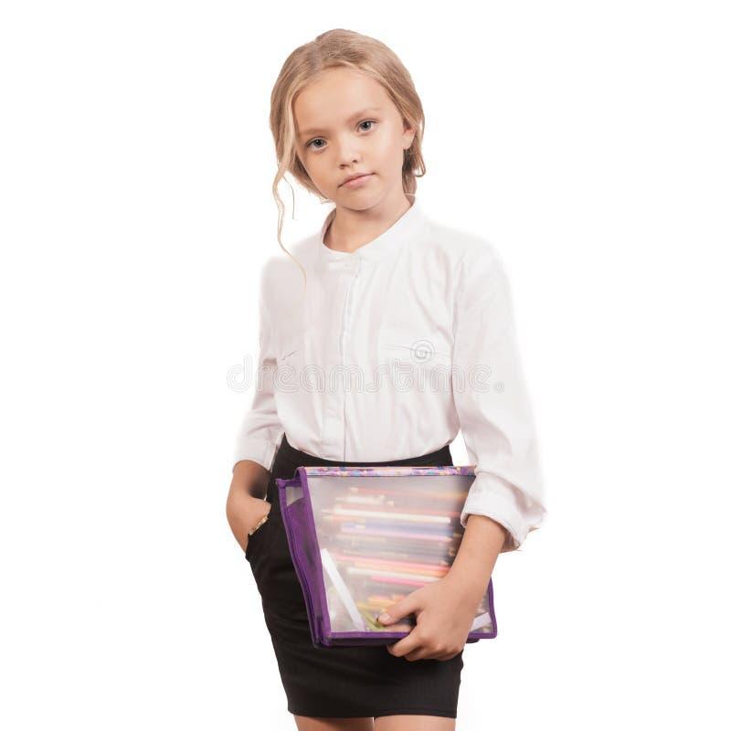 Porträt eines lächelnden Schulmädchens in der Uniform mit Bleistiftkasten stockfoto