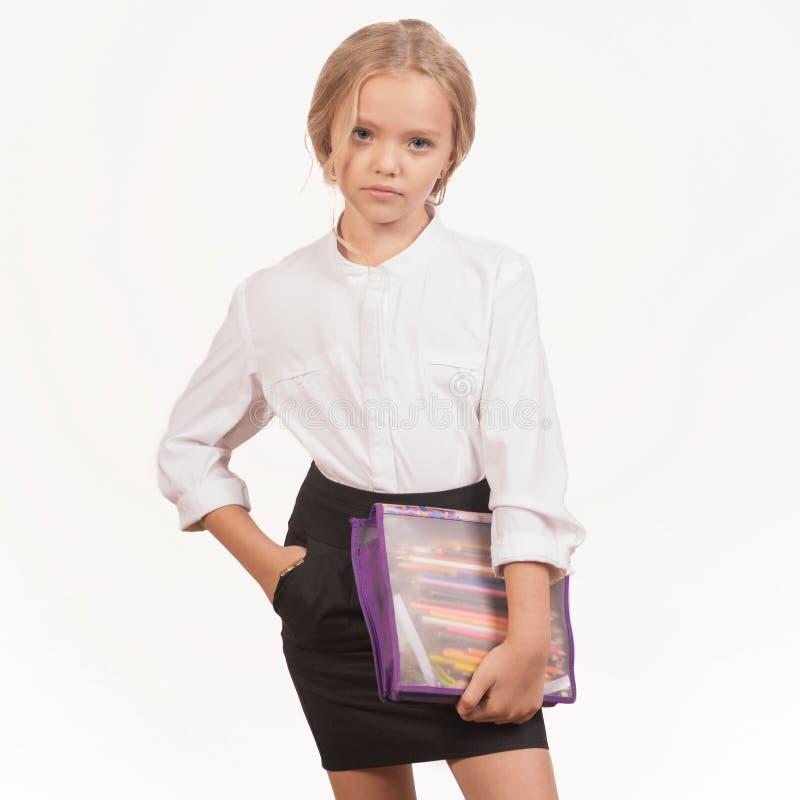 Porträt eines lächelnden Schulmädchens in der Uniform mit Bleistiftkasten lizenzfreie stockfotos
