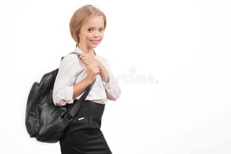 Porträt eines lächelnden Schulmädchens in der Uniform mit Schulrucksack stockfotos