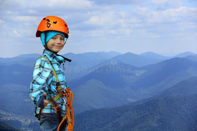 Porträt eines lächelnden sechs tragenden Sturzhelms des Jährigjungen und kletternder Sicherheitsgurt in den Bergen stockbild