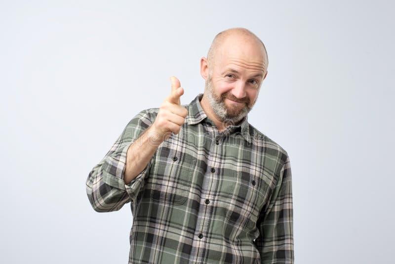Porträt eines Lächelns stellte den Mann zufrieden, der auf Sie zeigt, lokalisierte auf einem grauen Hintergrund, wie, Sie sagend, lizenzfreies stockbild