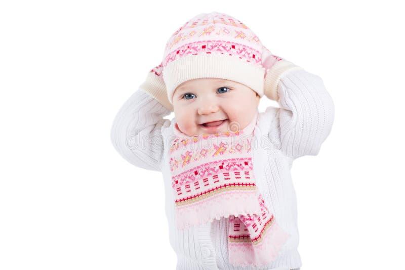 Porträt eines lustigen Babys in einer Strickmütze, in einem Schal und in einem Handschuh lizenzfreies stockbild