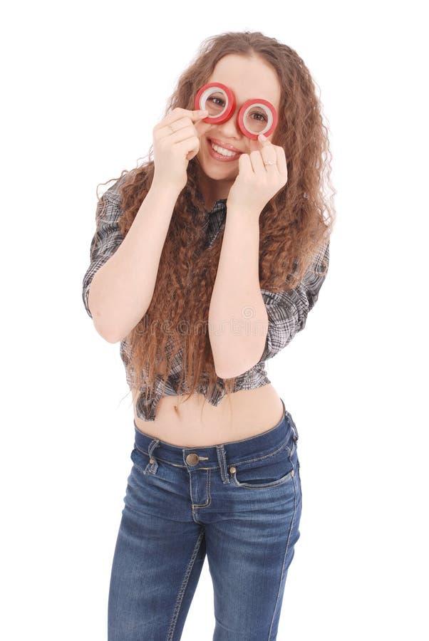 Porträt eines lustigen jungen Mädchens, das Kamera durch Isolierband betrachtet lizenzfreie stockbilder