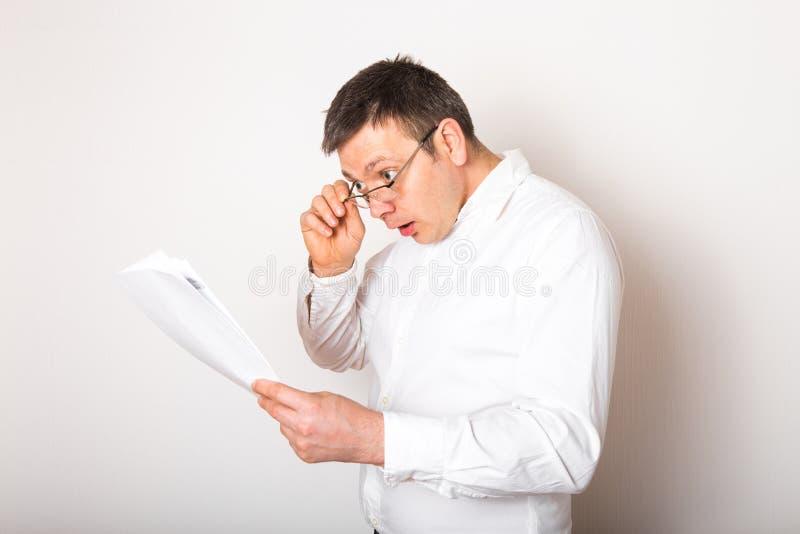 Porträt eines lustigen, kaukasischen Geschäftsmanns schockiert mit offenen Brillen, um Finanzberichte zu sehen, schlechte Nachric stockbild