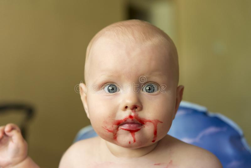 Porträt eines lustigen Kindes geschmiert mit Himbeersaft stockfotografie