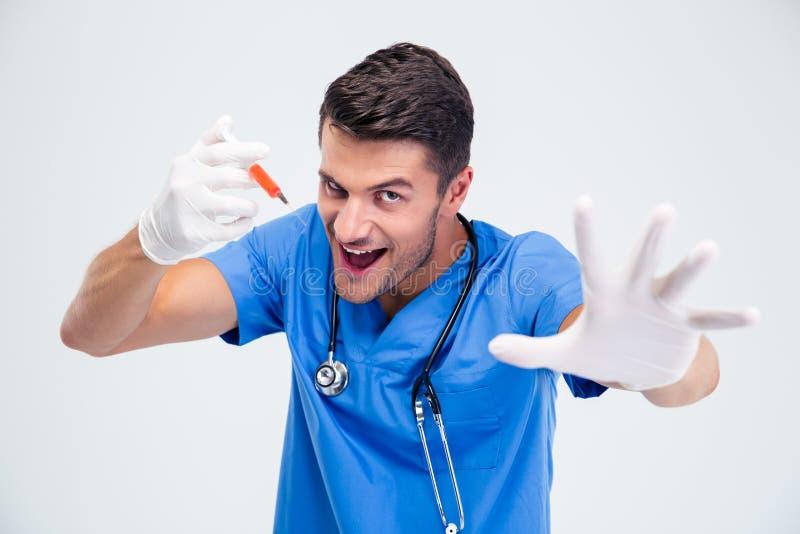 Porträt eines lustigen männlichen Doktors mit Spritze stockbilder