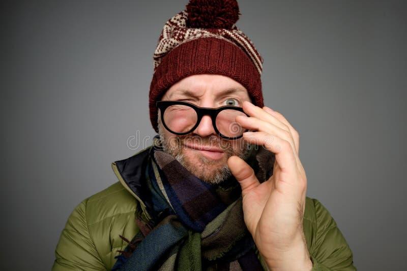 Porträt eines lustigen reifen Mannes im warmen Winter kleidet das Betrachten der Kamera durch Gläser über grauem Hintergrund stockbild