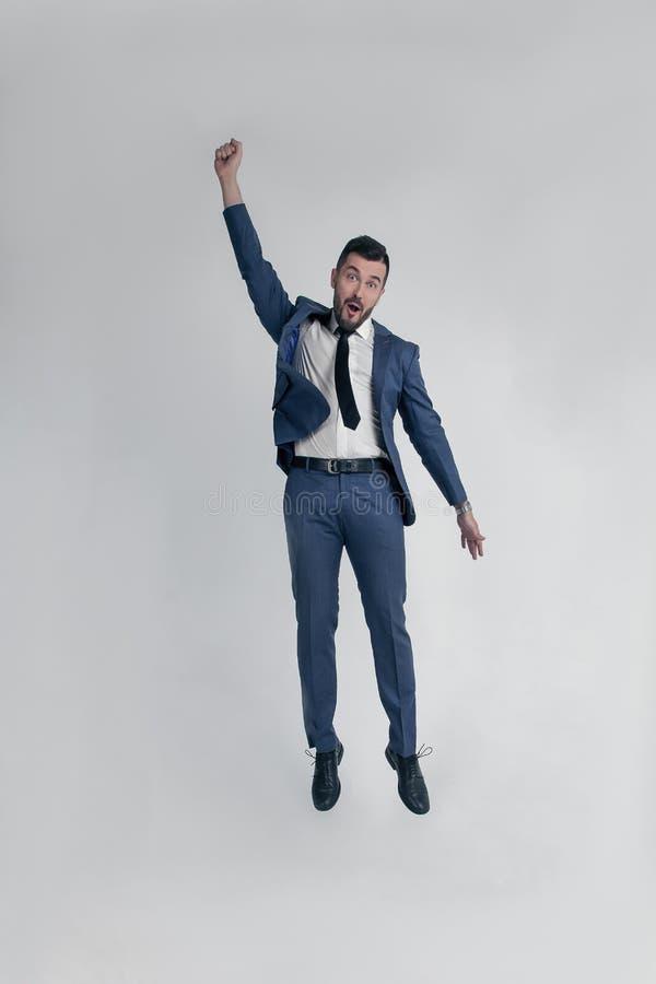 Porträt eines lustigen und kleinen verrückten Geschäftsmannmannes, der lautes lokalisiert auf einem weißen Hintergrund springt un lizenzfreie stockbilder