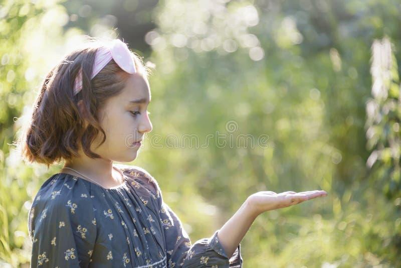 Porträt eines Mädchens, das eine Palme vor ihr hält stockfoto