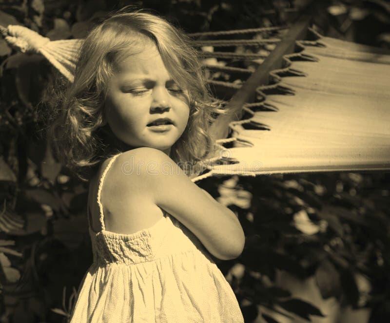 Porträt eines Mädchens, das ihre Augen vom Sonnenlicht und die Stellung nahe einer Hängematte bedeckte stockfoto