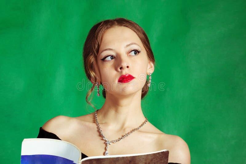 Porträt eines Mädchens in einem decollete Abendkleid, mit einer Zeitschrift in ihren Händen stockbild