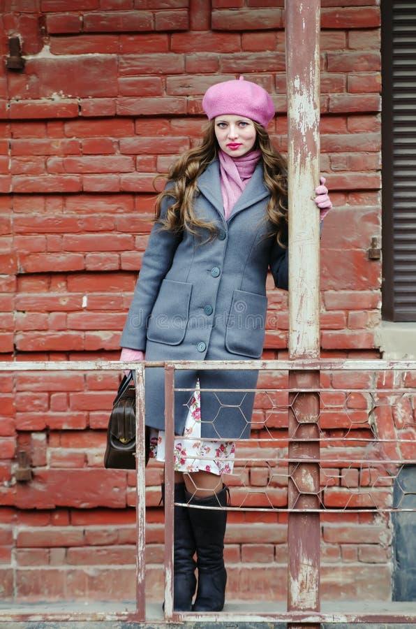 Porträt eines Mädchens in einem grauen Mantel und in einem rosa Barett in der Straße der alten Stadt lizenzfreies stockfoto