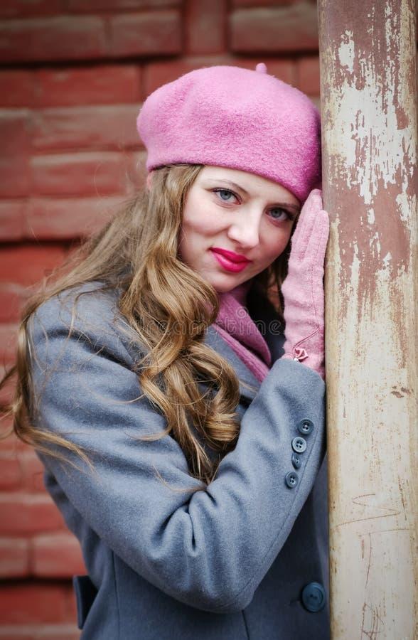 Porträt eines Mädchens in einem rosa Barett und in einem grau-blauen Mantel lizenzfreie stockfotografie