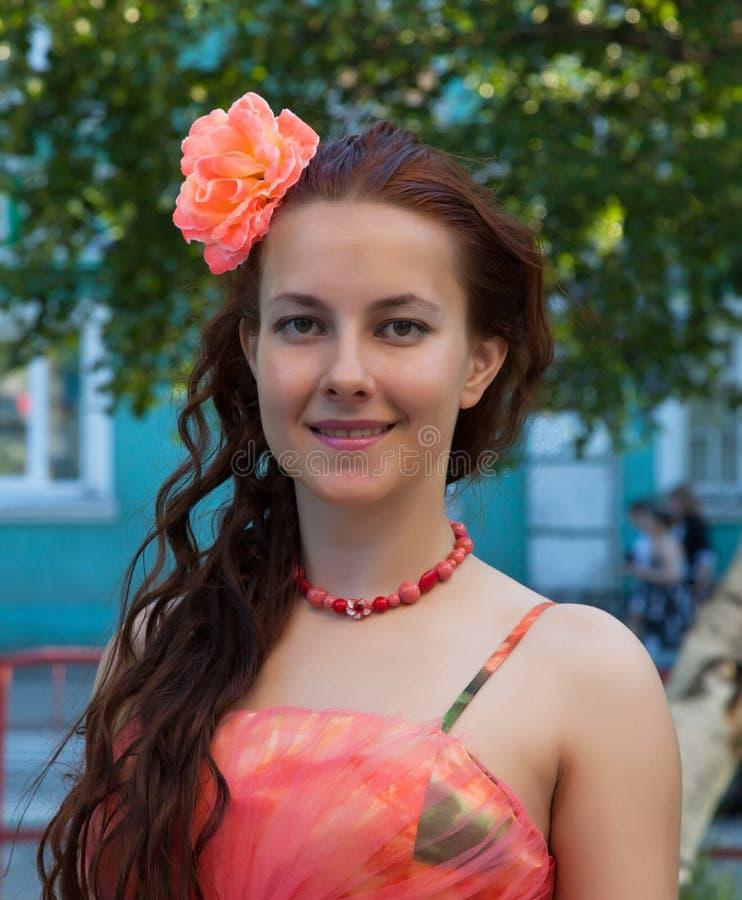 Porträt eines Mädchens in einem rosa Kleid mit einer Blume in ihrem Haar lizenzfreies stockfoto