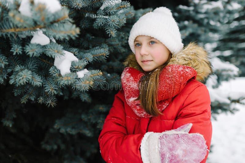 Porträt eines Mädchens in einer roten Jacke, nahe dem grünen Baum auf der Straße lizenzfreie stockbilder