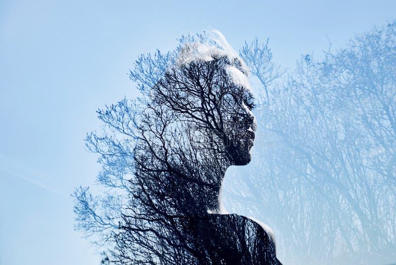 Porträt eines Mädchens mit Doppelbelichtung gegen eine Baumkrone Empfindliches mysteriöses Porträt einer Frau mit einem blauen Hi stockbild