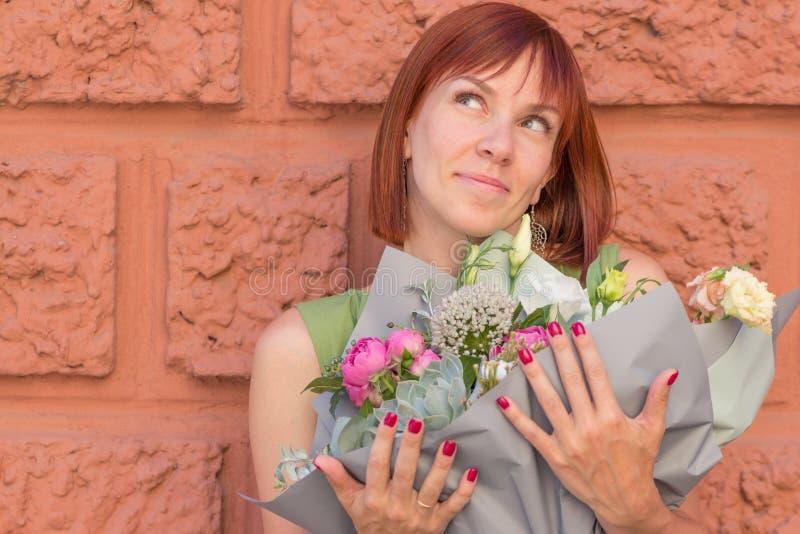 Porträt eines Mädchens mit einem stilvollen Blumenstrauß auf dem Wandhintergrund stockfoto