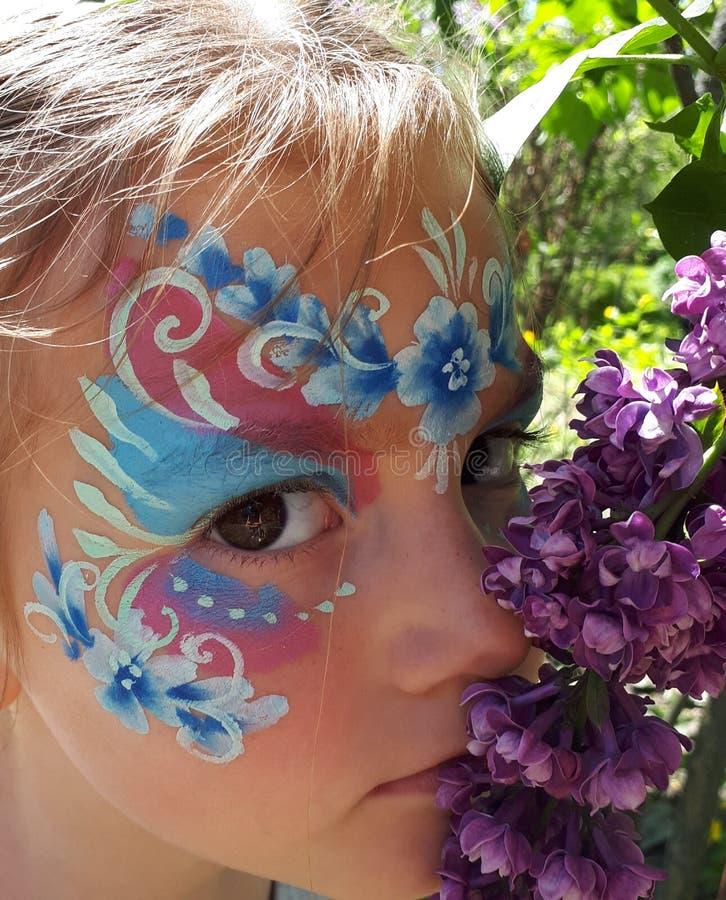 Porträt eines Mädchens mit einer Gesichtsmalerei, großen braunen Augen und einer Niederlassung der Flieder stockfotografie
