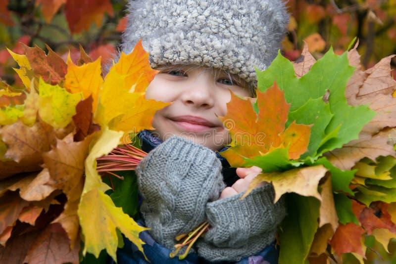 Porträt eines Mädchens umgeben durch die Herbstnatur, die bunte gefallene Blätter hält stockfotografie