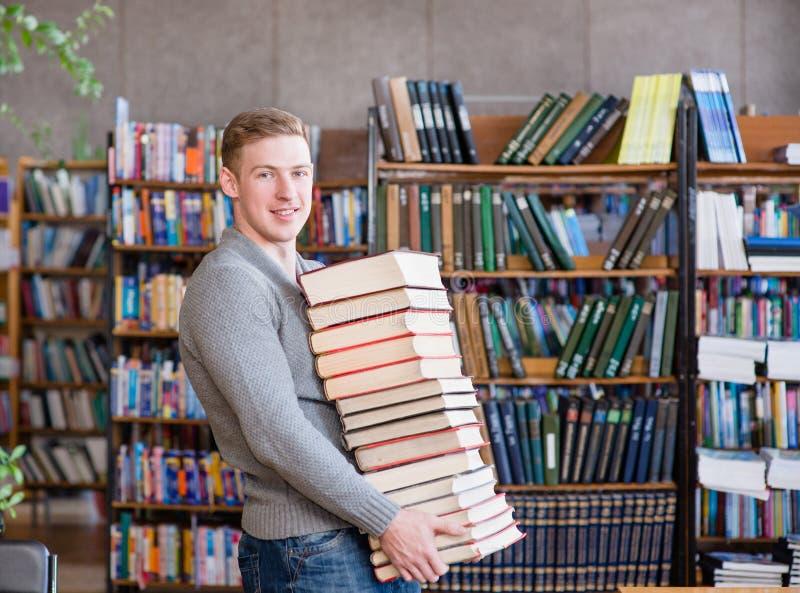Porträt eines männlichen Studenten mit Stapel bucht in der Collegebibliothek lizenzfreie stockfotos