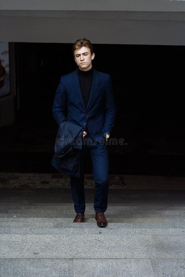 Porträt eines Mannes, auf der Straße, in einem Anzug und mit einem Mantel oben steigt die Schritte aus der Dunkelheit, Erfolg her stockfotografie