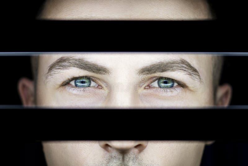 Porträt eines Mannes in der Dunkelheit im Licht der Lampen Atmosphärisches Kunstfoto eines Kerls mit grünen Augen Das Mann ` s Ge stockbild
