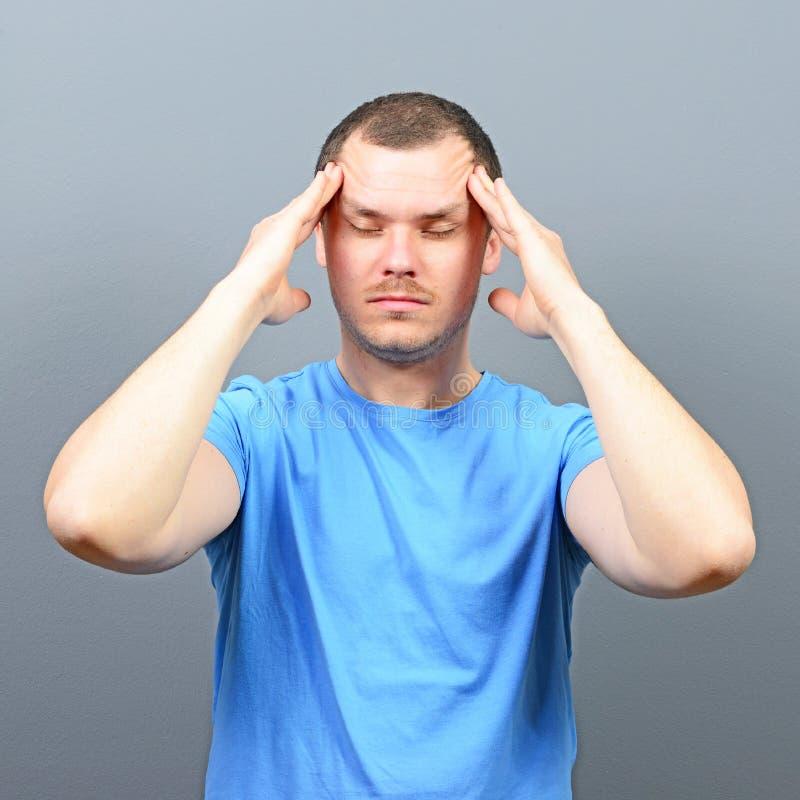 Porträt eines Mannes, der Finger auf Stirn setzt und versucht sich zu konzentrieren lizenzfreie stockfotografie