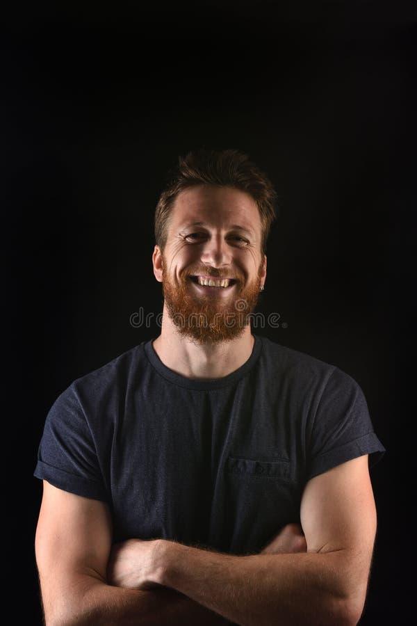 Porträt eines Mannes, der lächelt und mit den Armen gekreuzt und schwarzem Hintergrund stockfoto