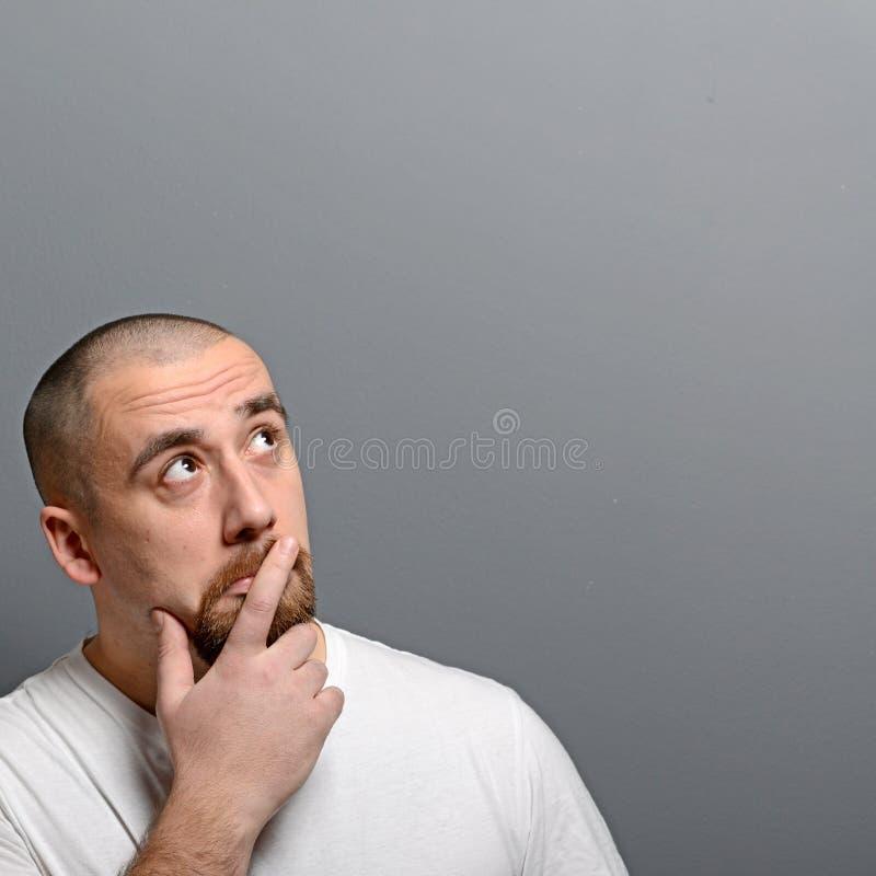 Porträt eines Mannes, der oben gegen grauen Hintergrund denkt und schaut lizenzfreies stockfoto