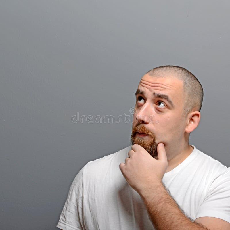 Porträt eines Mannes, der oben gegen grauen Hintergrund denkt und schaut stockbild