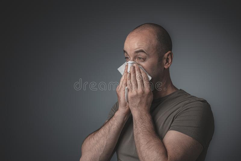 Porträt eines Mannes, der seine Nase mit einem Gewebe durchbrennt lizenzfreie stockbilder