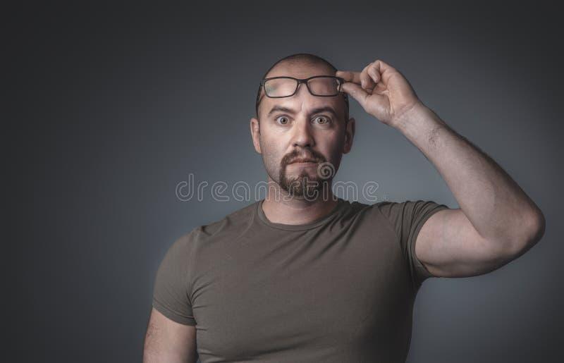 Porträt eines Mannes mit überraschtem Ausdruck, der seine Gläser anhebt stockfotos