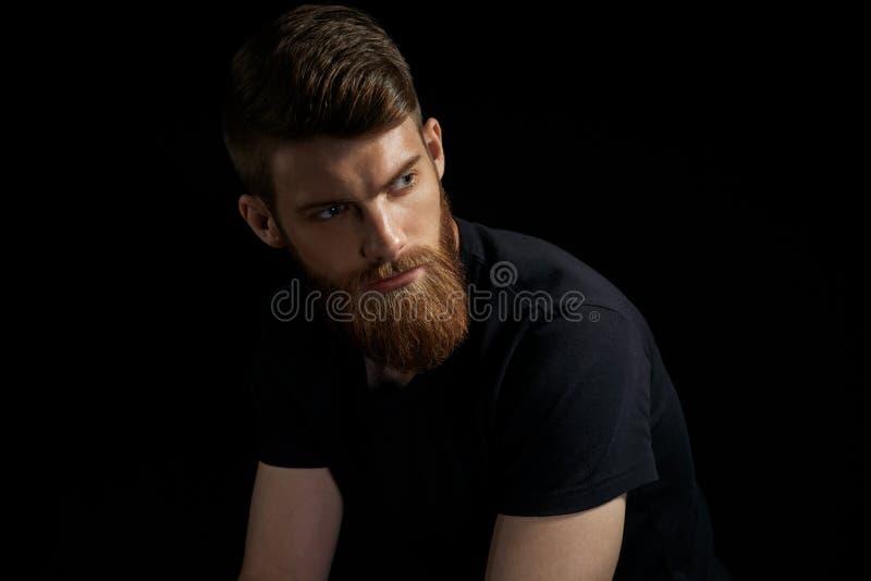 Porträt eines Mannes mit Bart und moderner Frisur stockfotografie