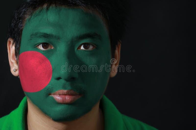 Porträt eines Mannes mit der Flagge Bangladeschs malte auf seinem Gesicht auf schwarzem Hintergrund lizenzfreies stockfoto