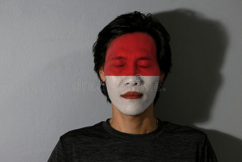 Porträt eines Mannes mit der Flagge des Indonesiens malte auf seinem Gesicht und nahen Augen mit schwarzem Schatten auf grauem Hi stockfotos