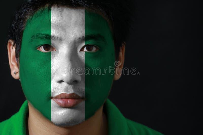 Porträt eines Mannes mit der Flagge des Nigerias malte auf seinem Gesicht auf schwarzem Hintergrund lizenzfreies stockfoto
