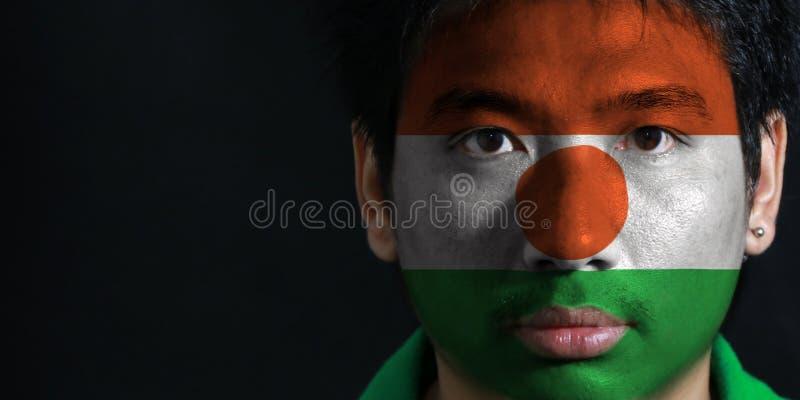 Porträt eines Mannes mit der Flagge des Nigers malte auf seinem Gesicht auf schwarzem Hintergrund stockfoto