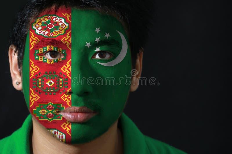 Porträt eines Mannes mit der Flagge des Turkmenistans malte auf seinem Gesicht auf schwarzem Hintergrund lizenzfreies stockbild