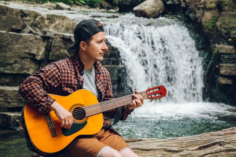 Porträt eines Mannes spielt eine Gitarre, die auf einem Stamm eines Baums gegen einen Wasserfall sitzt Raum für Ihre Textnachrich stockfotografie