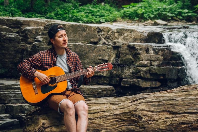 Porträt eines Mannes spielt eine Gitarre, die auf einem Stamm eines Baums gegen einen Wasserfall sitzt Raum für Ihre Textnachrich lizenzfreie stockfotos