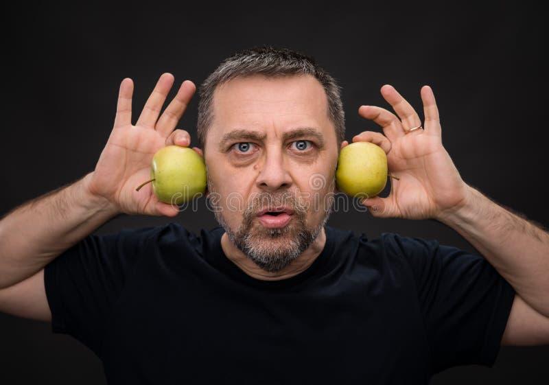 Mann von mittlerem Alter mit grüne Äpfel lizenzfreie stockfotos
