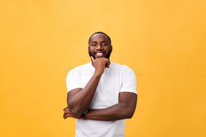 Porträt eines modernen jungen schwarzen Mannes, der mit den Armen gekreuzt auf gelbem Hintergrund lächelt stockbild